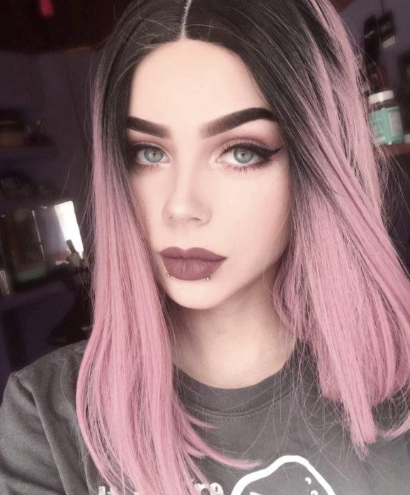 Cabello color rosa cherry blossom, flor de cerezo; chica de ojos azules, con cabello teñido y negro en las raíces, perforaciones en los labios