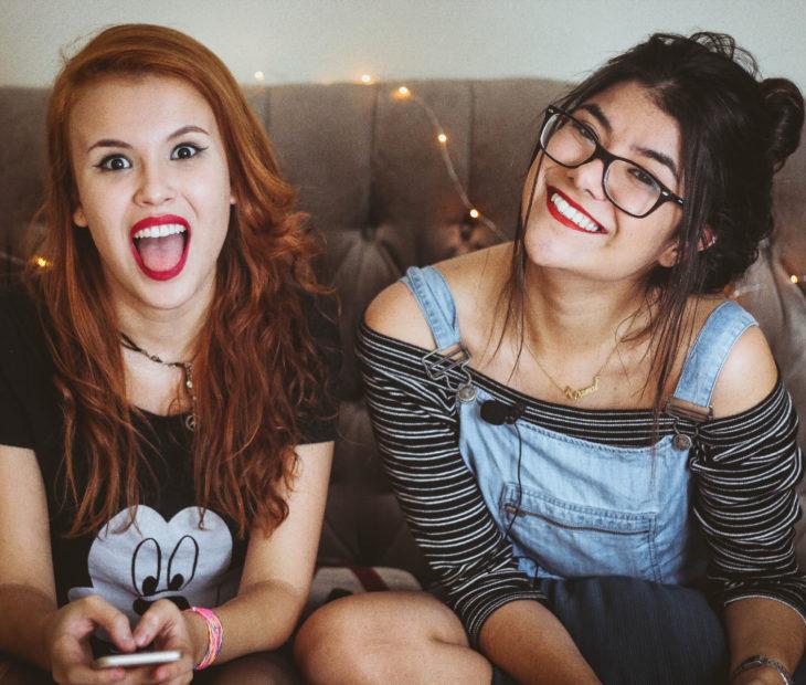 Amigas sentadas en un sillón sonriendo; chica de cabello rojo, largo y ondulado, haciendo gestos, mujer de cabello castaño peinado con chongo, messy bun, con overol