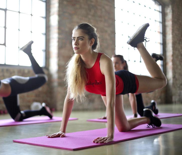 Chica en el gimnasio haciendo ejercicio, cabello rubio y peinado con una coleta