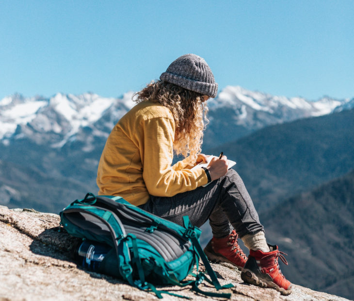 Chica sentada en la cima de una montaña, escribiendo y dibujando en una libreta