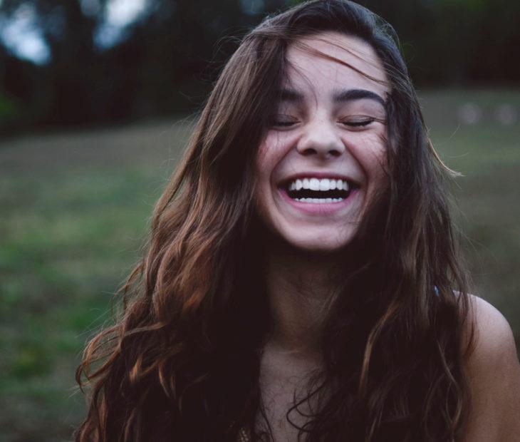 Chica sonriendo con los ojos cerrados
