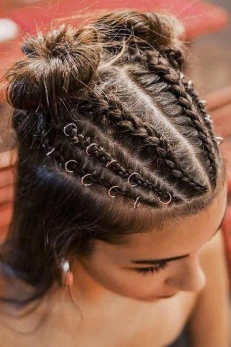 Chica de cabello largo y castaño con argollas en el cabello con trenzas