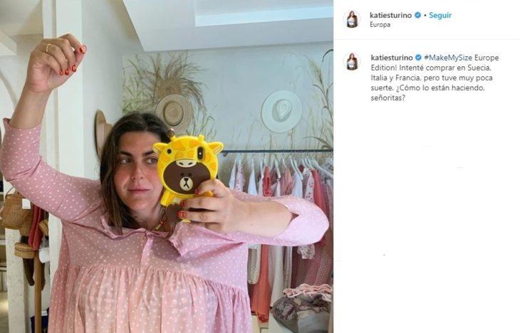 Katie Sturino tomando una selfie dentro de un provador con un vestido rosa palo que no va a acorde a su talla
