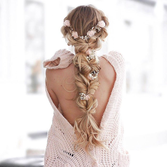 Chica rubia de cabello largo con trenza esponjosa con flores rosas