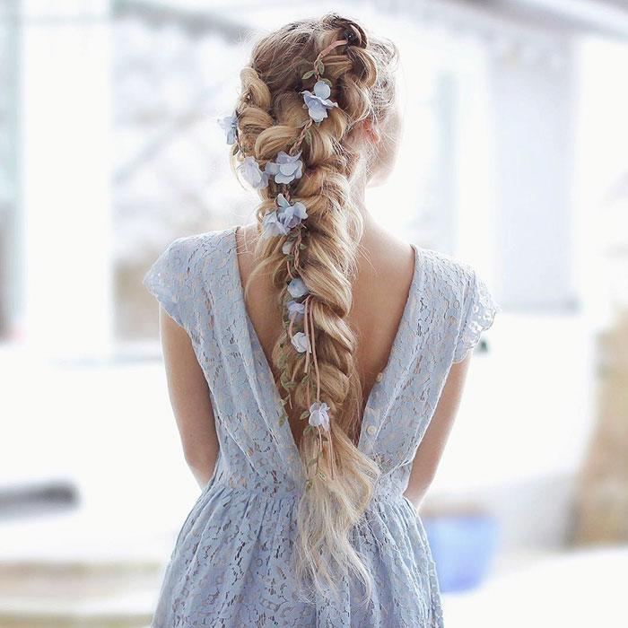 Mujer rubia con trenzas con mucho volumen con flores azules