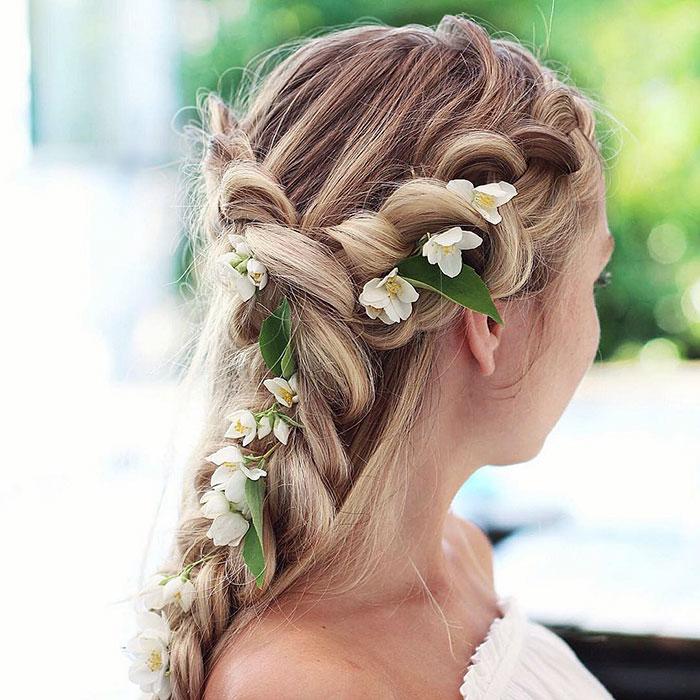 Chica rubia con trenza esponjosa con flores blancas y hojas verdes