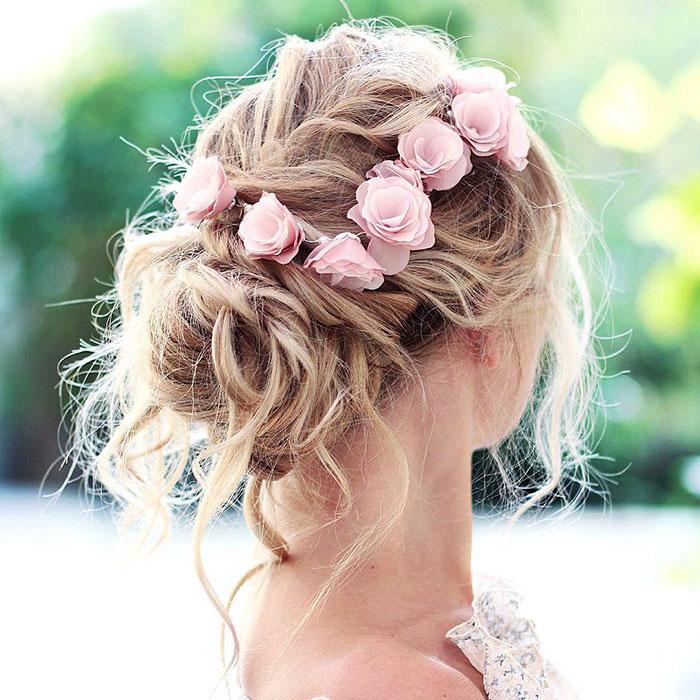 Mujer rubia con recogido suelto con flores rosas
