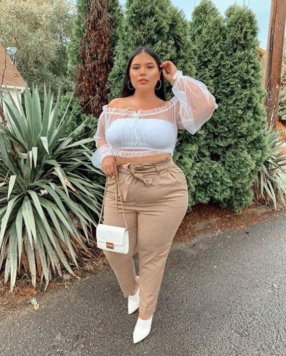 Chica curvy con blusa blanca con transparencias y pantalón beige