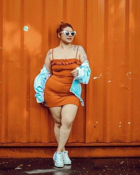 Chica curvy con vestido naranja de tirantes y chamarra de mezclilla