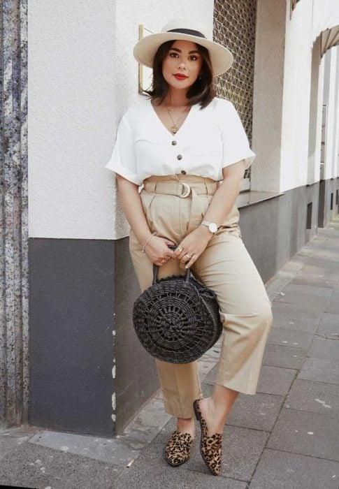 Chica curvy con pantalón beige amplio y blusa blanca
