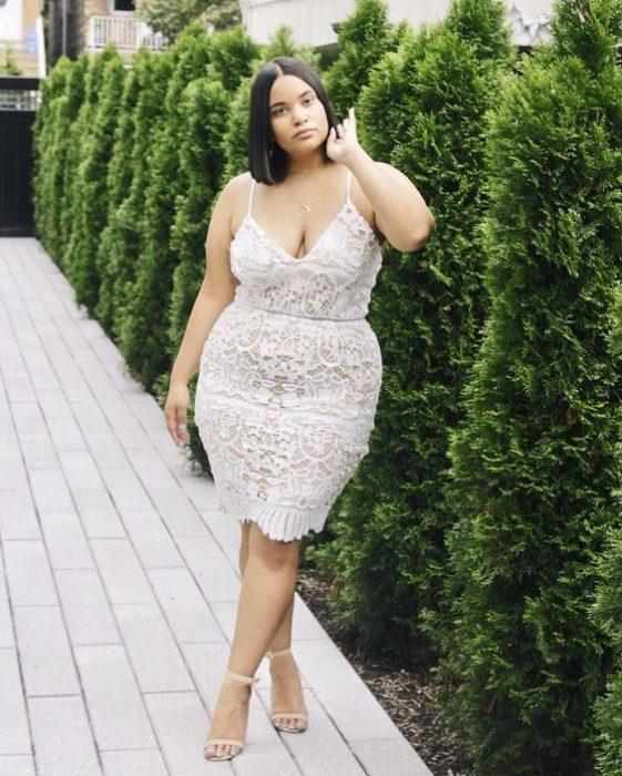 Chica curvy de menela corta con vestido ajustado blanco