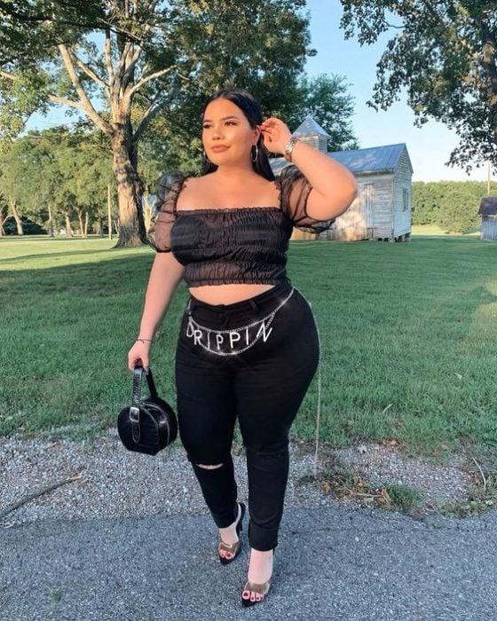 Chica curvy con blusa transparente negra y patanlón negro