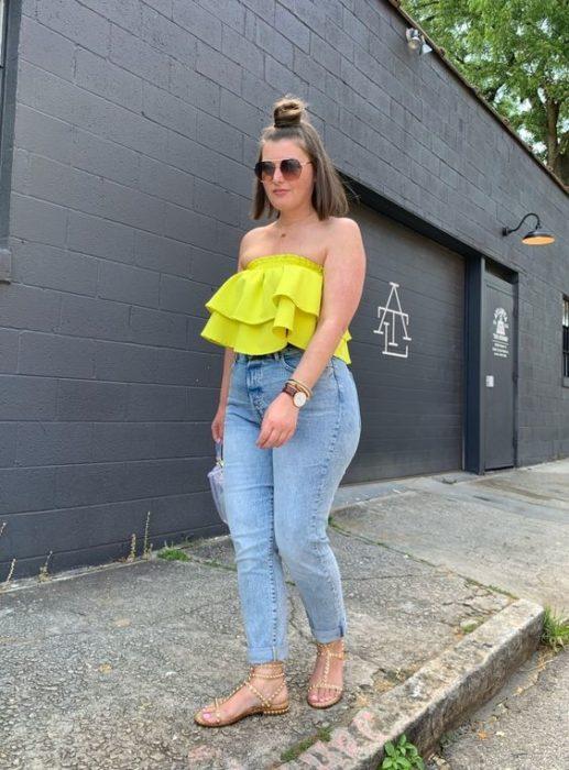 Chica curvy con blusa amarilla sin hombros y jeans