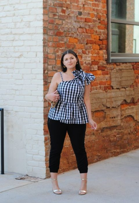 Curvy girl in checkered sleeveless top and jeans
