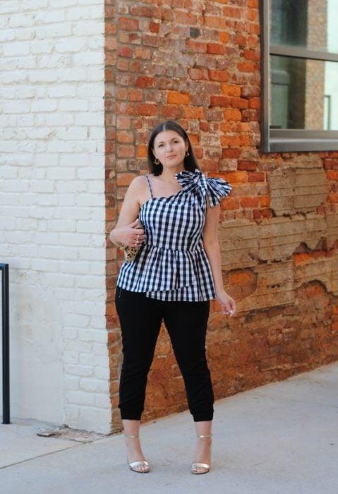 Chica curvy con blusa sin mangas con cuadros y jeans