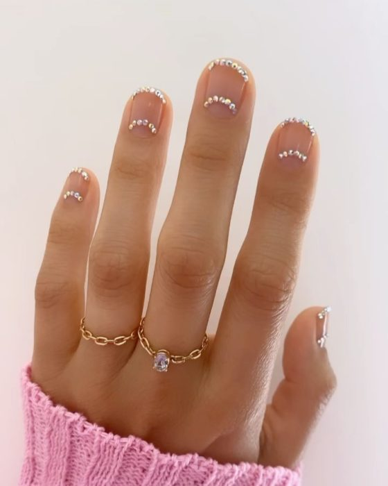Betina Goldstein nail designs with rhinestones on the bottom and top of the nails