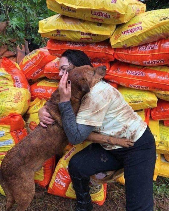 Mujer siendo abrazada por un perro al que llevó bultos de alimento