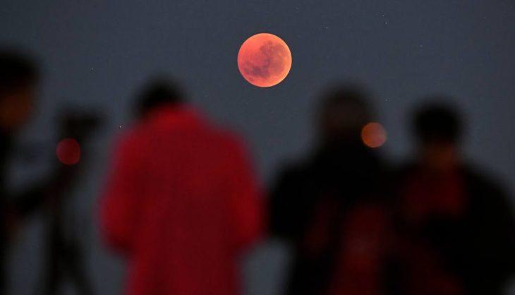 Personas mirando el eclipse lunar
