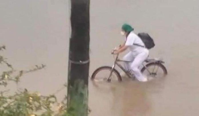 Enfermera manejando su bicicleta mientras las calles están inundadas y cae lluvia