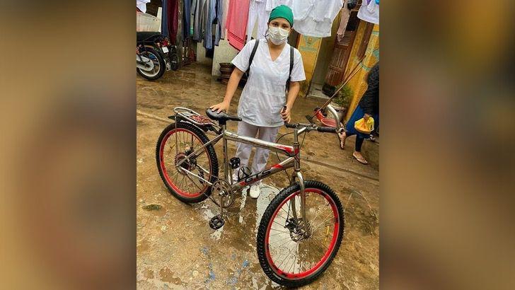 Enfermera sosteniendo su bicicleta después de regresar de trabajar en el hospital