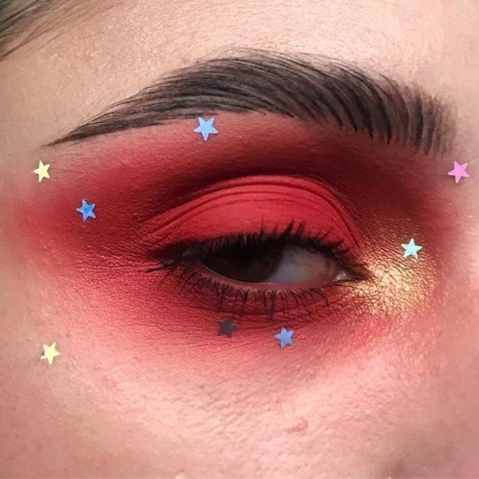 Maquillaje galáctico con tonos rojos y tornasol