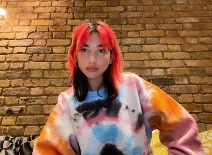 Dua Lipa con el cabello teñido en colores rosas con rojo en la parte inferior