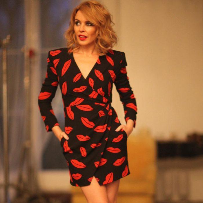 Kylie Minogue posando para una foto mientras usa un vestido de color negro con plumas en color rojo
