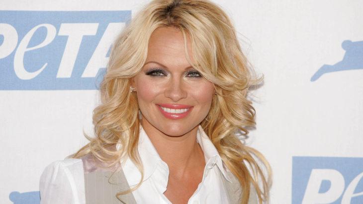 Pamela Andersonposando para una fotografía mientras se encuentra en una alfombra roja