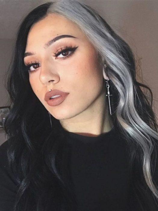 Chica de cabello largo y oscuro con un mechón beige y lentes estilo High-Contrast hair