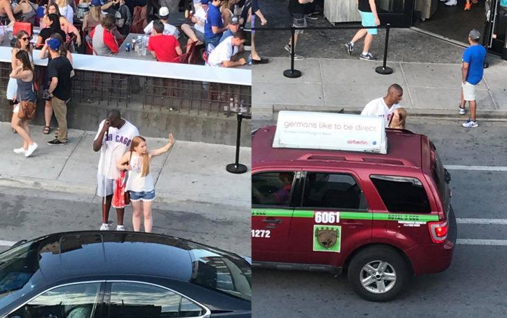 Chica en medio del trafico deteniendo un taxi para que un hombre ciego desconocido pueda subirse a un taxi