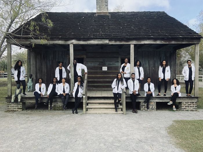 Personas de color paradas frente a una casa que perteneció a un grupo de esclavos de color