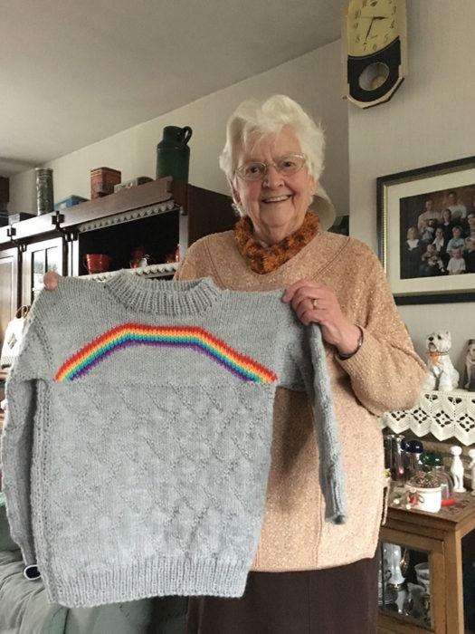 Mujer sosteniendo un sueter de color gris tejido con un arcoíris del orgullo Lgbtq