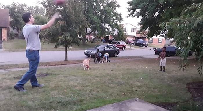 Hombre jugando con un niño a la pelota mientras están en el jardín delantero de una casa