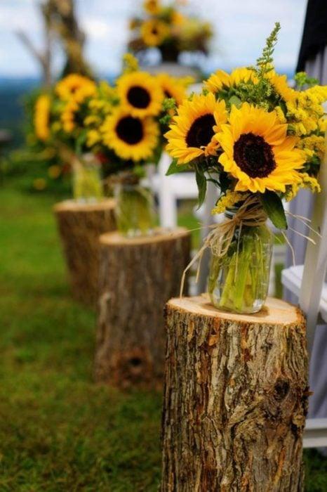 Decoración de boda con troncos y frascos con girasoles
