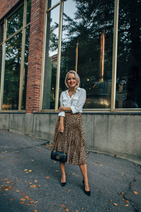Girl wearing an animal print midi skirt with a white silk blouse