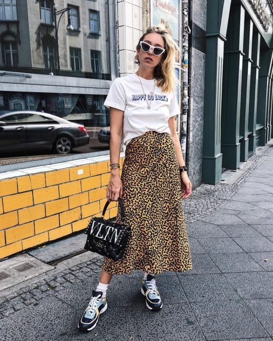Girl wearing an animal print midi skirt with a white print blouse