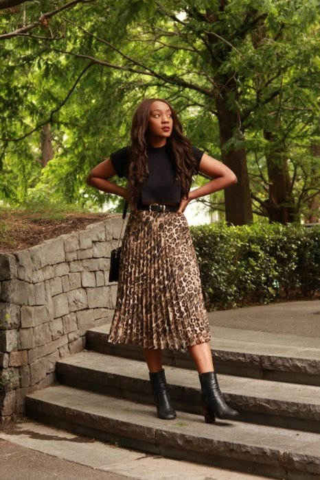 Girl wearing an animal print midi skirt with a black blouse