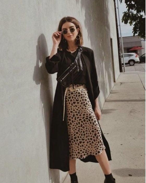 Chica usando una falda midi con estampado animal print con una blusa de color negro