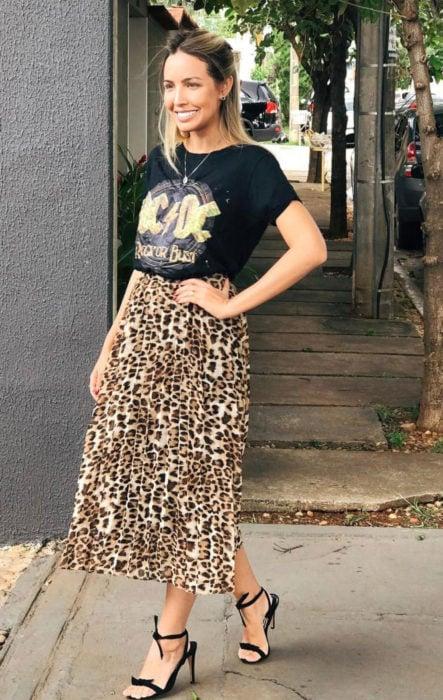 Chica usando una falda midi con estampado animal print con una blusa de color negro con el logo de AC/DC