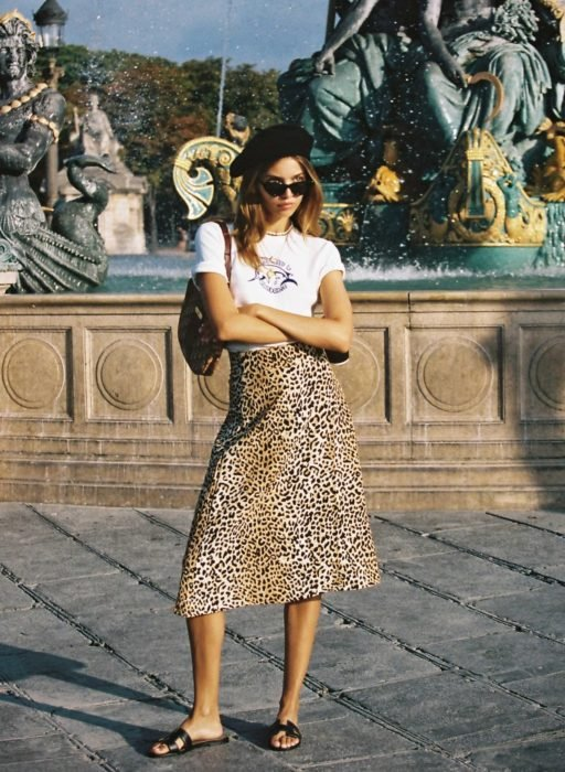 Girl wearing an animal print midi skirt with a white blouse
