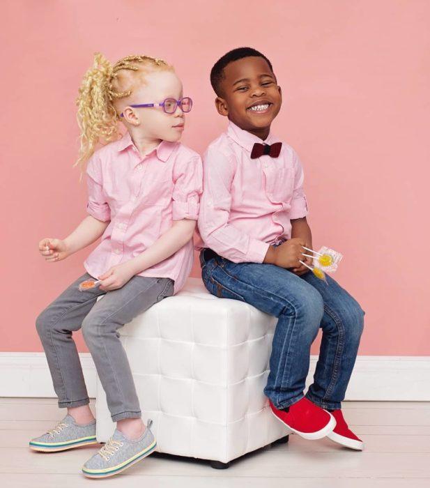 Kachi y Kamis sentados en un cubo usando camisas rosas