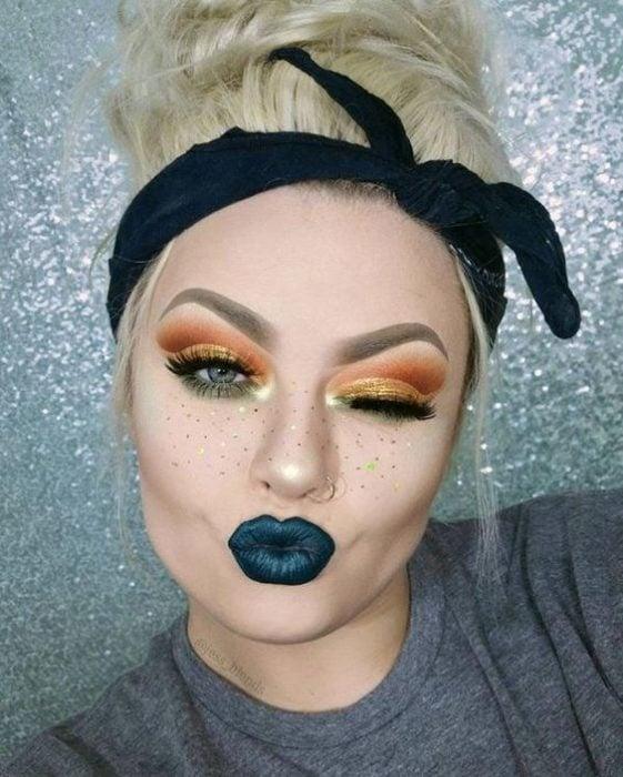 Chica rubia con cabello recogido con una pañoleta negra usa labial verde oscuro