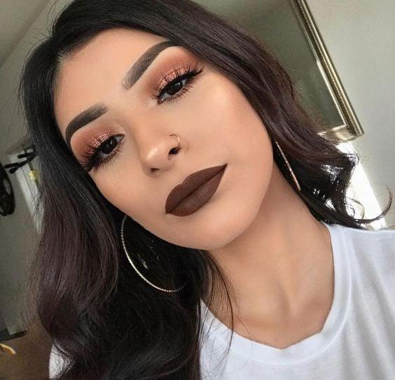 Chica latina de cabello largo y negro suelto usa labial marrón