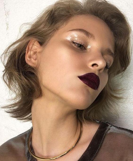 Modelo rubia de melena corta posa con labial cereza