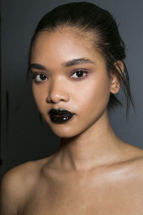 Modelo de piel morena usa labial y gloss de color negro