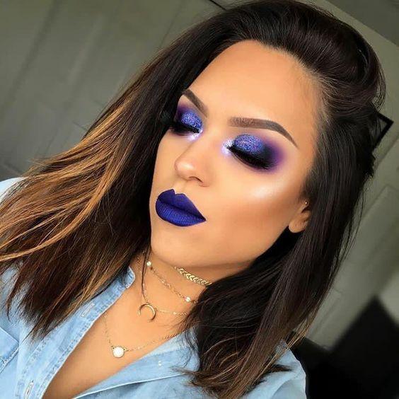 Mujer morena con melena castaña usa maquillaje de ojos extravagante y labial azul