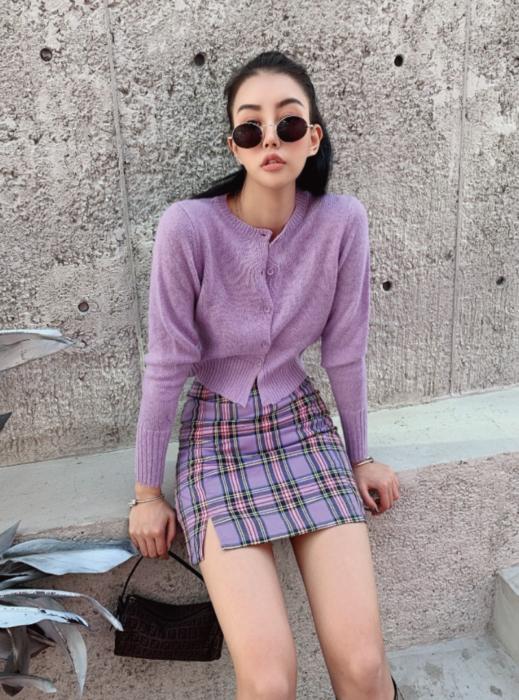 Chica usando falda con estampado tartán y suéter delgado color lavanda