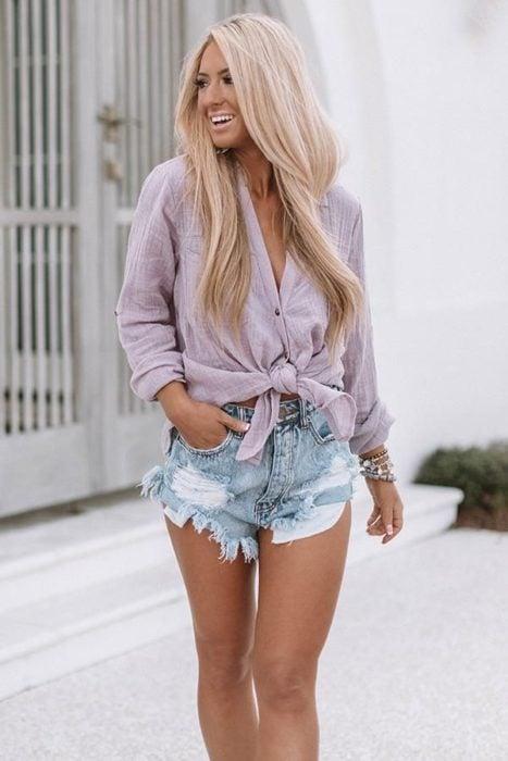 Chica usando camisa anudada color lavanda con shorts de mezclilla