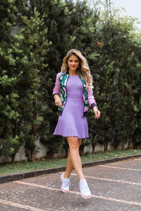 Chica usando vestido ajustado color lavanda con una bomber jacket