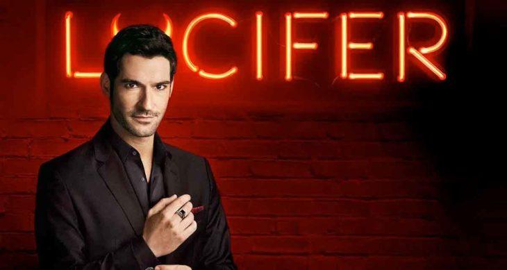 Tom Ellis, actor, acomodando el puño de su camisa negra, posando de perfil y llevando un traje en tono oscuro.